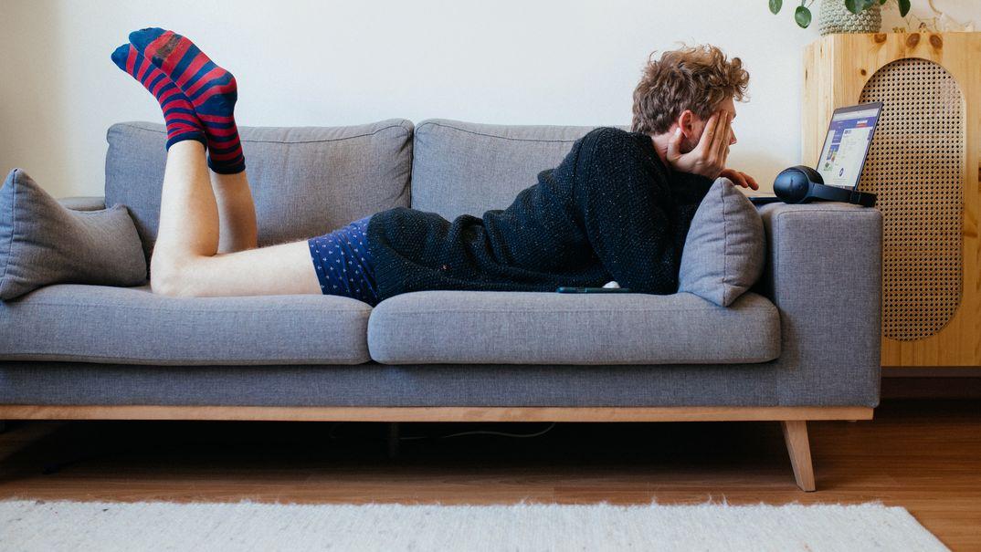 Mann auf Couch mit Notebook