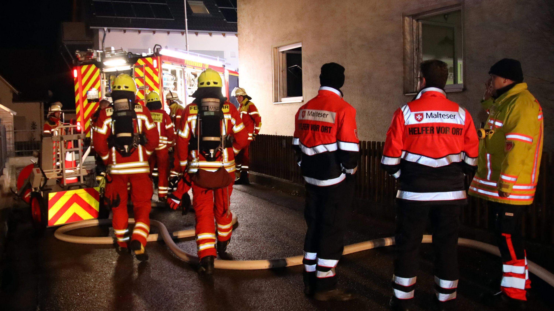 Feuerwehrleute und Rettungssanitäter stehen vor einem Haus