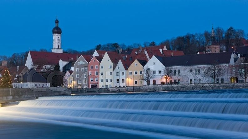 Staustufe im Lech, im Hintergrund die Stadt Landsberg im Abendlicht