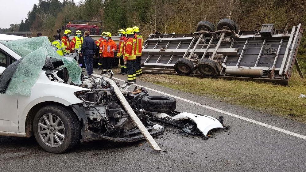 Das total zerstörte Auto, Einsatzkräfte und ein umgekippter Lkw-Anhänger an der Unfallstelle