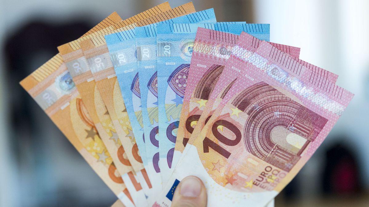 Eine Hand hält einen Bündel Geldscheine in die Luft