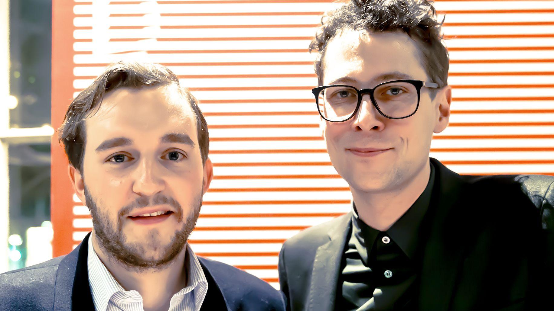 Zwei Männer in Jacket blicken vor einer rotweißgestreiften Wand frontal in die Kamera