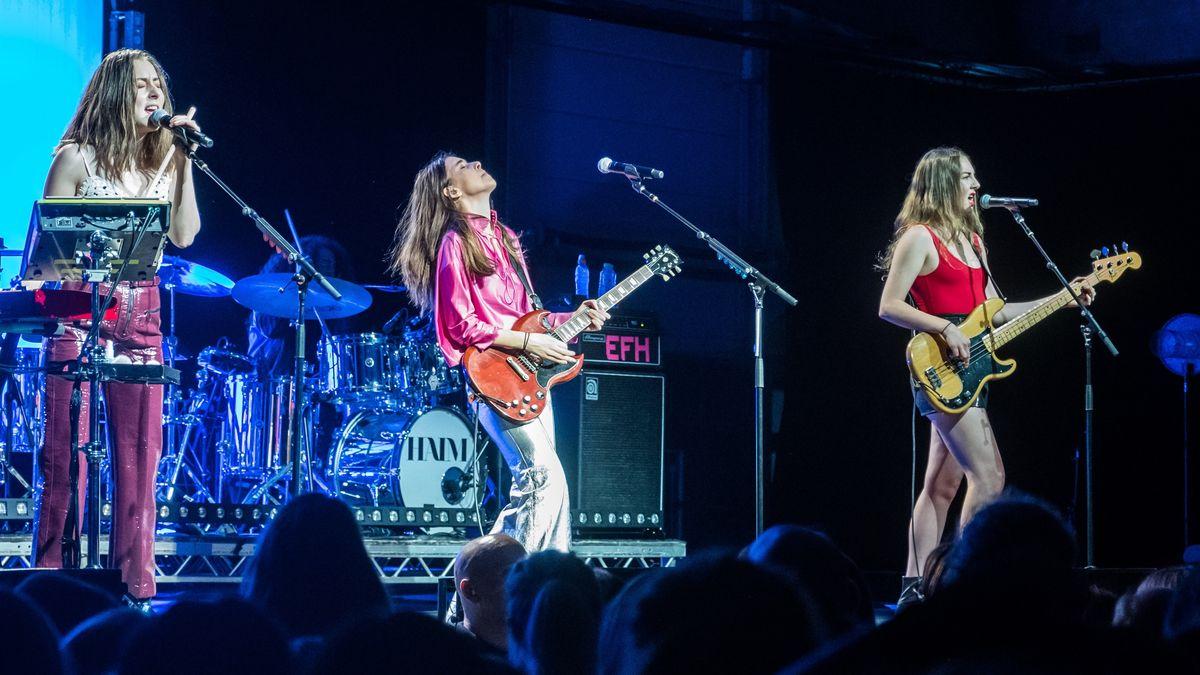 Drei Frauen auf einer Musikbühne, eine singt, eine spielt E-Gitarre, eine Bass-Gitarre.