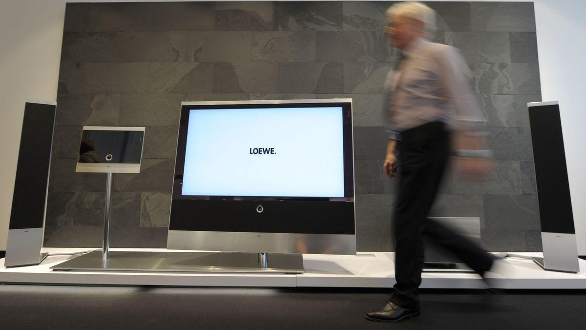 Ein Mann läuft vor einem ausgestellten Fernsehgerät der Marke Loewe.