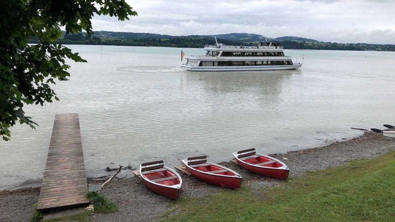Am Forggensee: Drei Boote liegen am Ufer neben einem Steg, auf dem See fährt ein Ausflugsboot