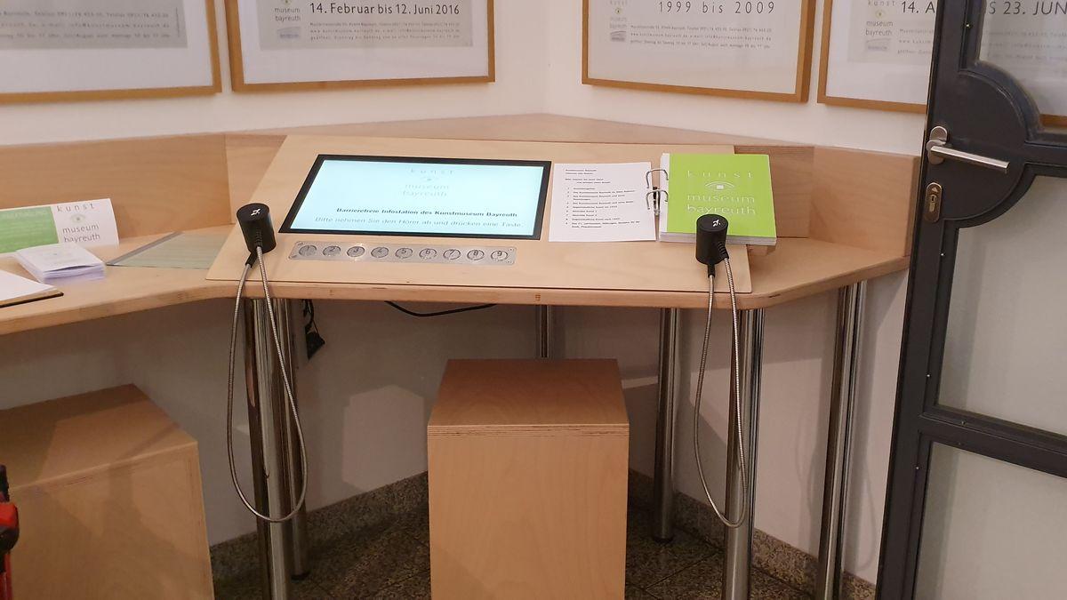 Auf einem Holztisch ist eine Konsole mit einen Monitur und unterschiedlichen Knöpfen angebracht.