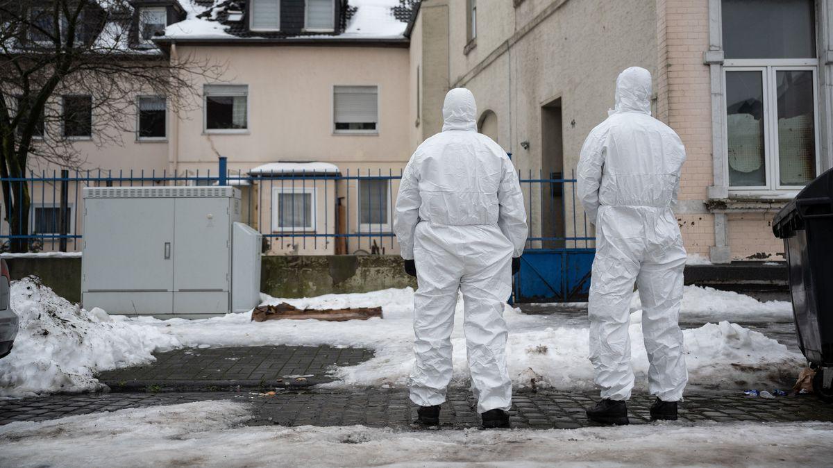 Zwei Einsatzkräfte der Polizei stehen vor einem Gebäude und tragen Schutzanzüge.