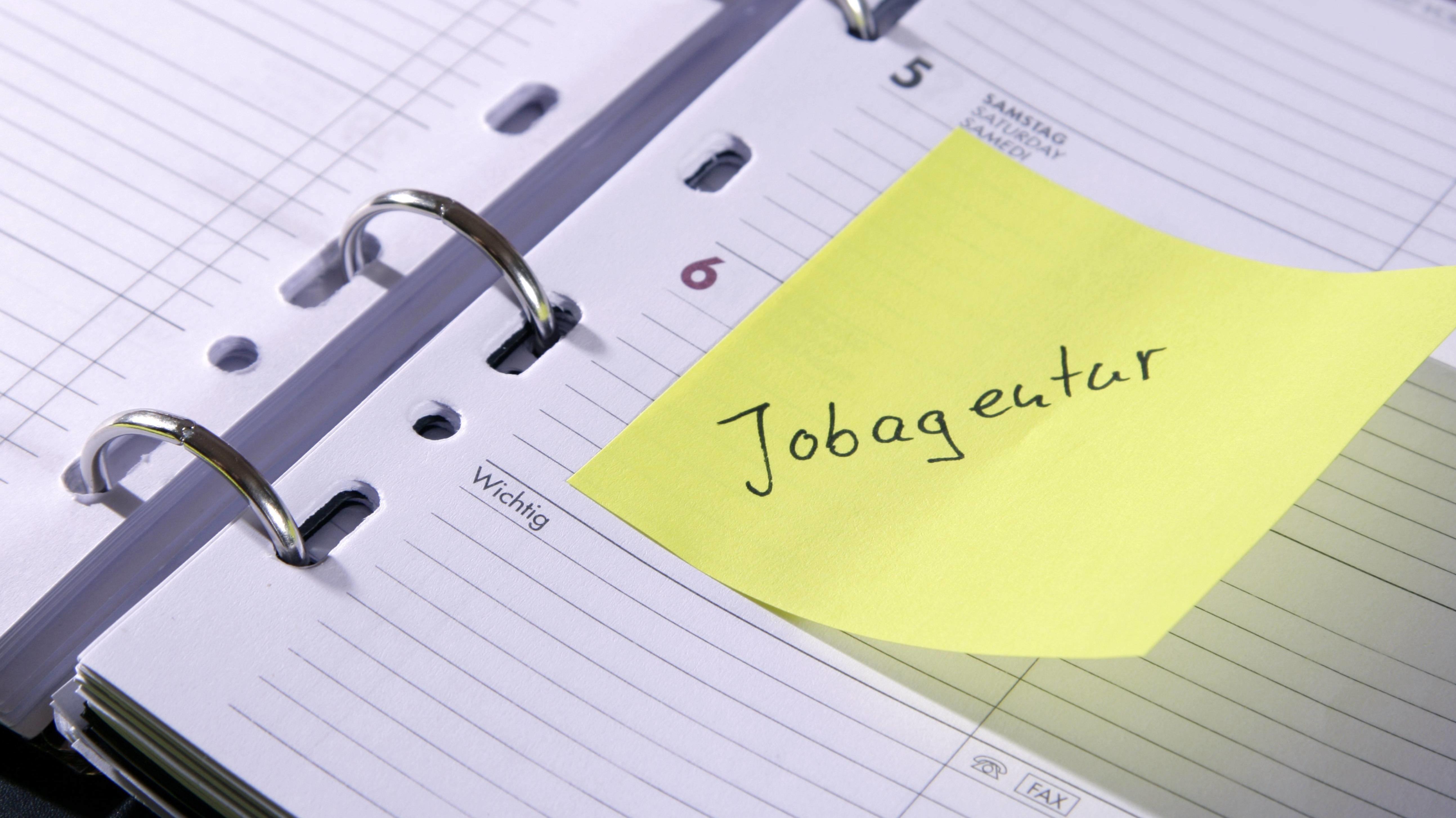 Notizzettel im Terminkalender mit der Aufschrift 'Jobagentur'