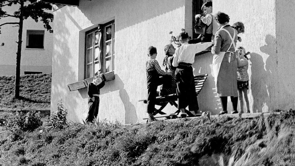 Kinder und Betreuerin in einem SOS-Kinderdorf, 50er-Jahre | Bild:picture alliance / Oscar Poss