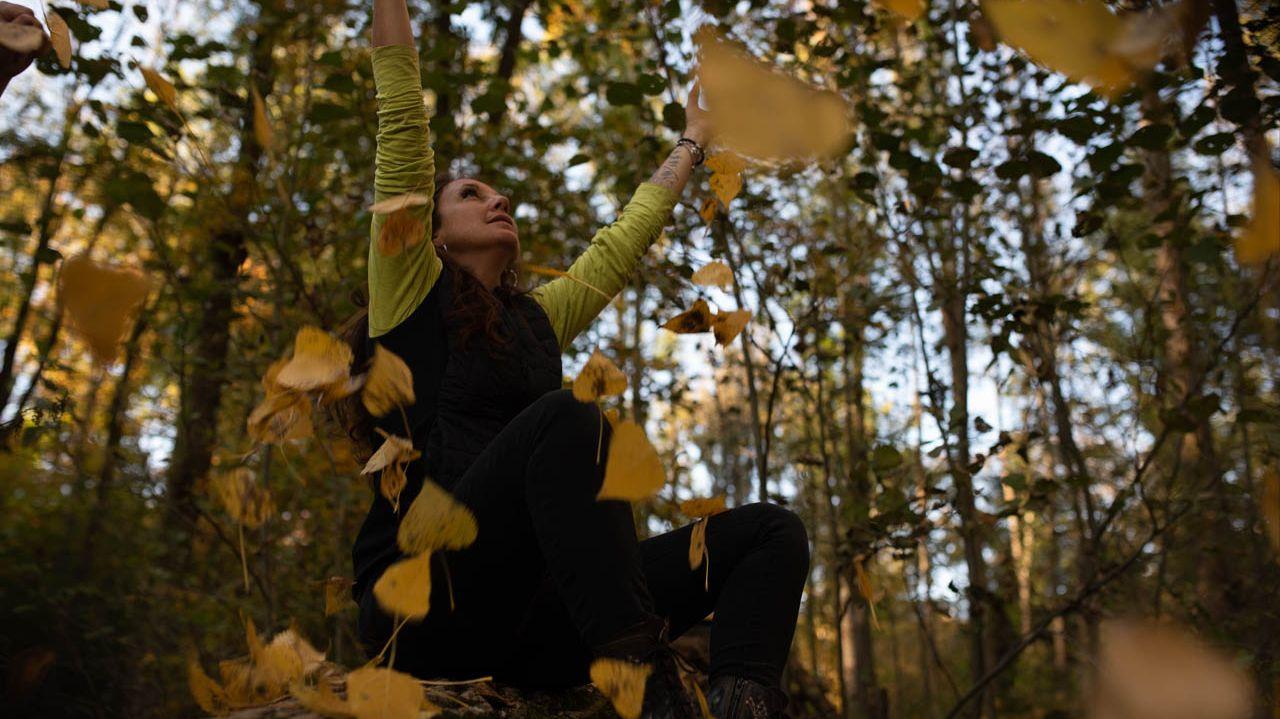 """Claudia Müller beim """"Waldbaden"""", sitzt zwischen Bäumen und wirft Laub in die Luft."""