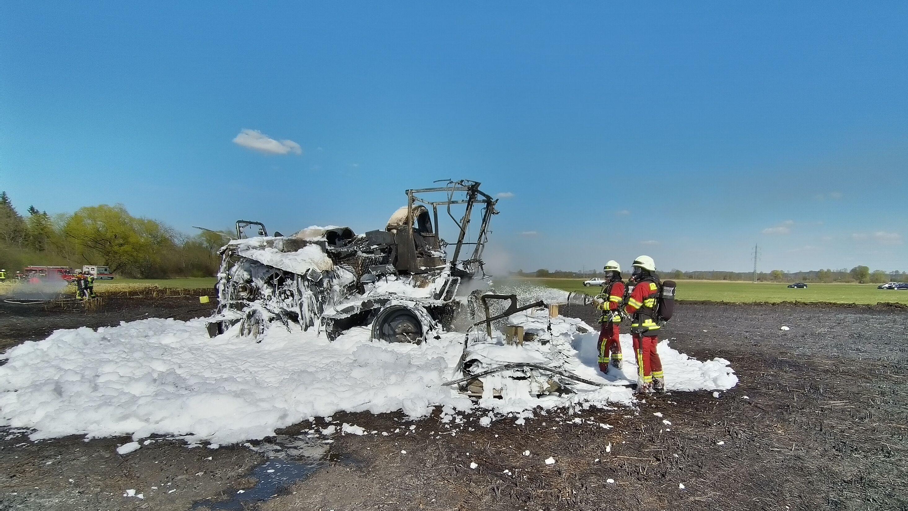 Feuerwehrleute stehen in einem Teppich aus Löschschaum vor dem ausgebrannten Maishäcksler.