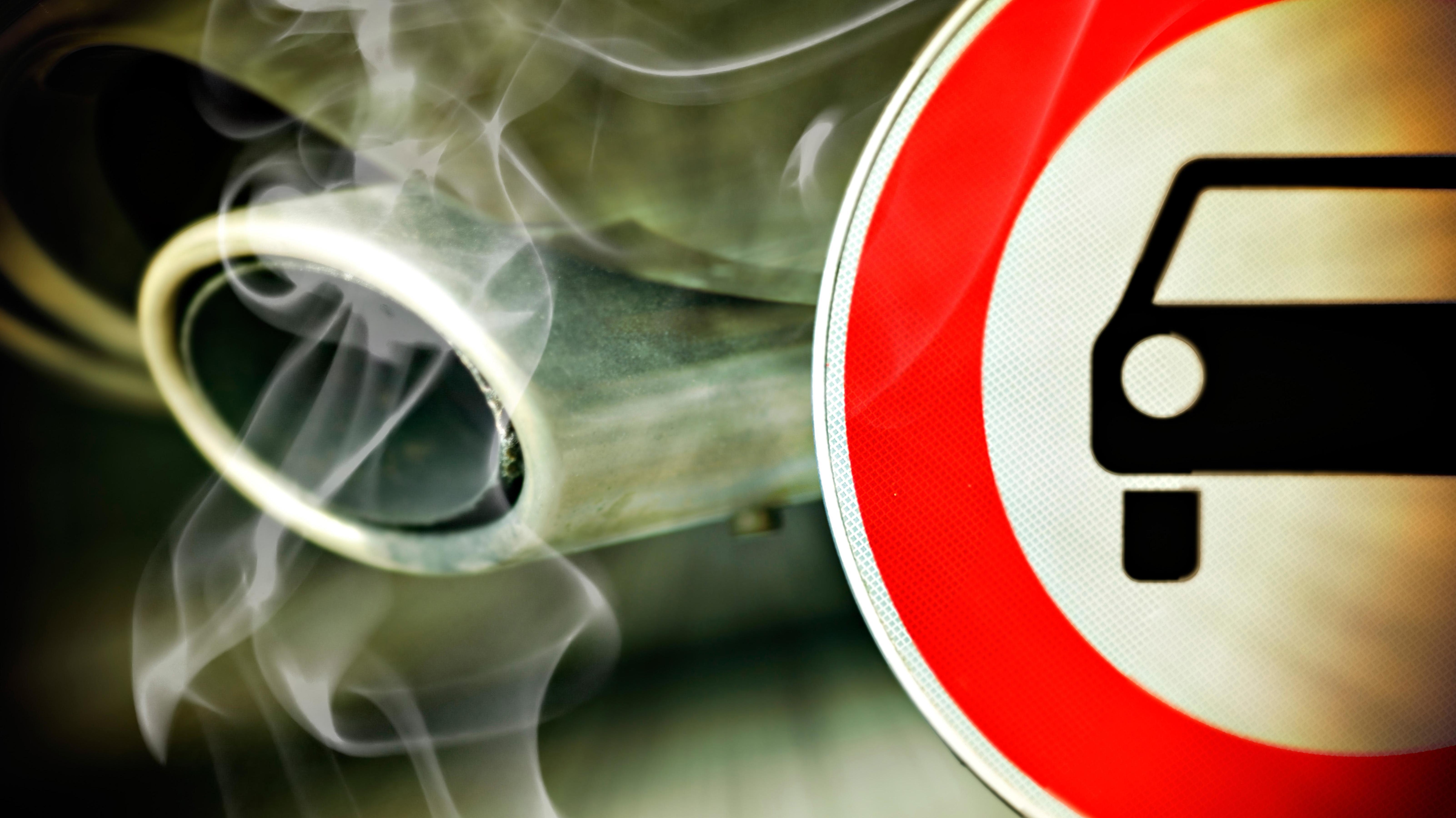 Verbotsschild und Autoauspuff mit Abgasen