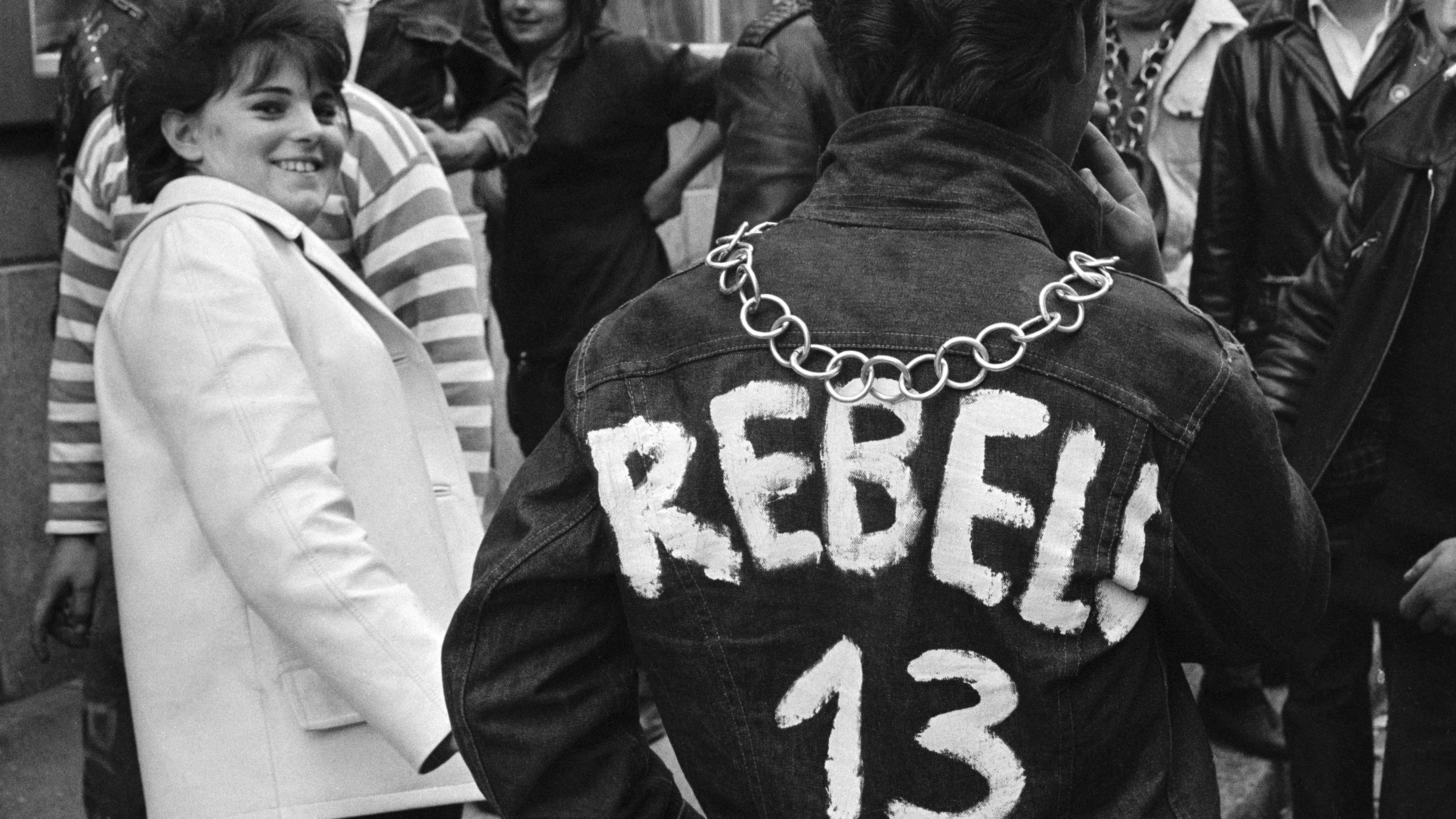 """Halbstarke in Zürich, 1963: Junge mit beschrifteter Jeansjacke (Aufschrift: """"Rebel!"""") wird von einer jungen Frau im weißen Mantel angesehen"""