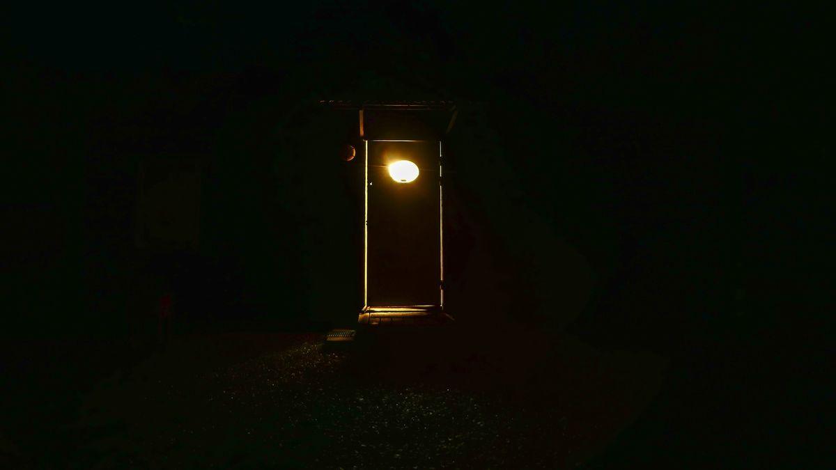 In total dunkler Nacht fällt Licht durch ein ovales Türfenster und den Spalt unter der Tür.