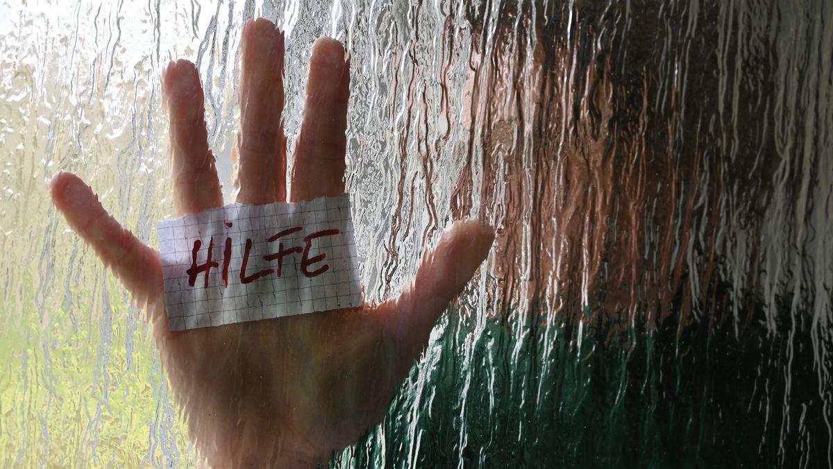 """Eine Hand an einer Glasscheibe mit einem Zettel auf dem """"Hilfe"""" steht"""