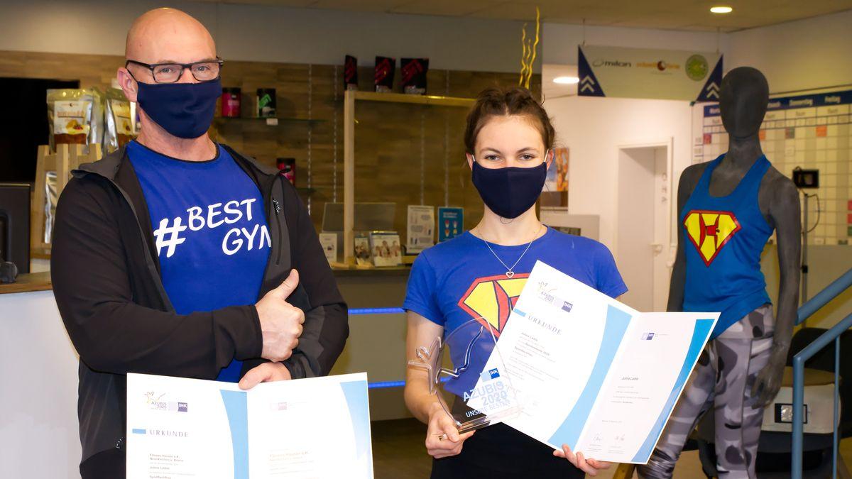 Die Absolventin Julina Laible und ihr Ausbilder Bernhard Hauser halten die Abschlussurkunde der IHK in die Kamera. Wegen der Corona-Pandemie tragen beide einen Mund-Nase-Schutz.