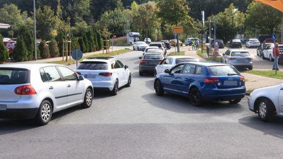 Autos warten in zwei Reihen vor einer Tankstelle.