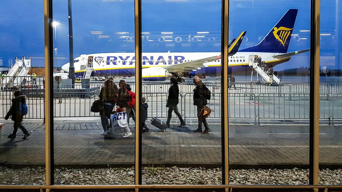 Mehrere Menschen mit Koffern und Taschen gehen zwischen Absperrgittern zu einem Flugzeug mit der Aufschrift Ryanair.