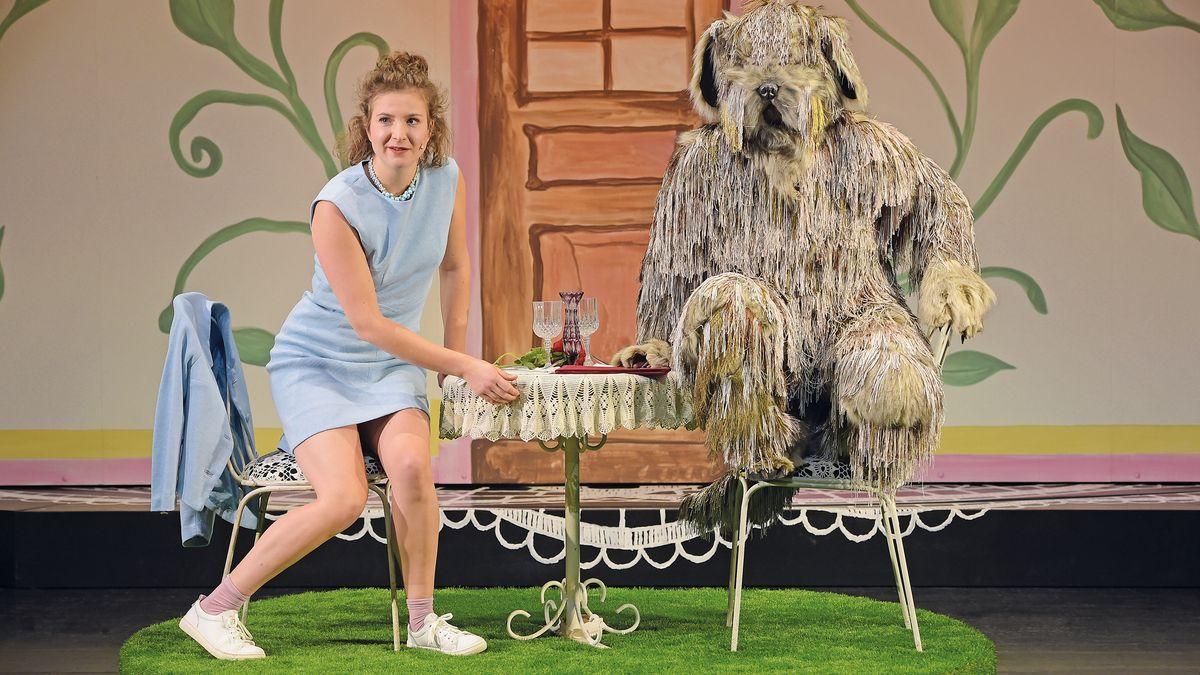 Eine Schaupielerin im blauen Kleid sitzt an einem Tisch, an dem ein als Hund verkleideter Schauspieler ebenfalls auf einem Stuhl Platz genommen hat.