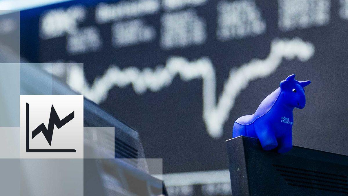 Blauer Stier aus Gummi sitzt auf der oberen Kante eines Bildschirmes, im Hintergrund die Kurstafel der Börse