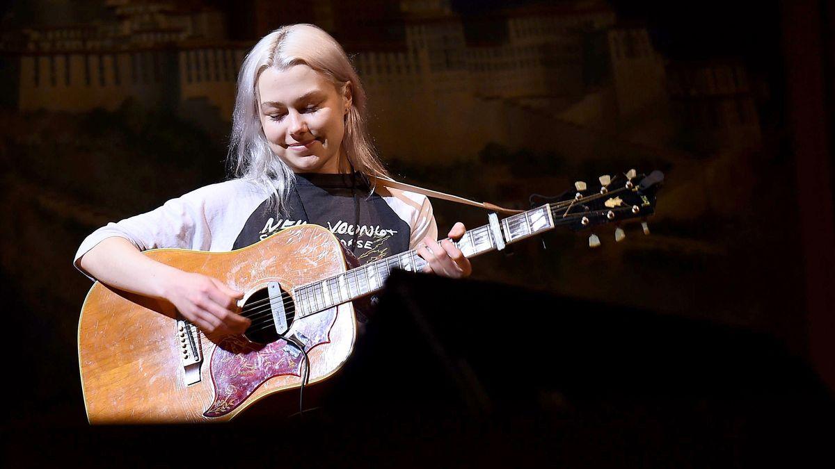 Songschreiberin Phoebe Bridgers mit akustischer Gitarre auf dunkler Bühne