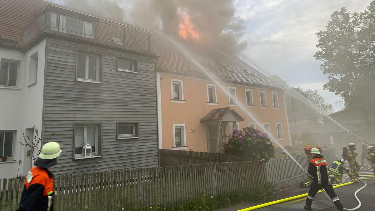 Mehrere Feuerwehrleute halten Lösch-Schläuche auf einen brennenden Dachstuhl.