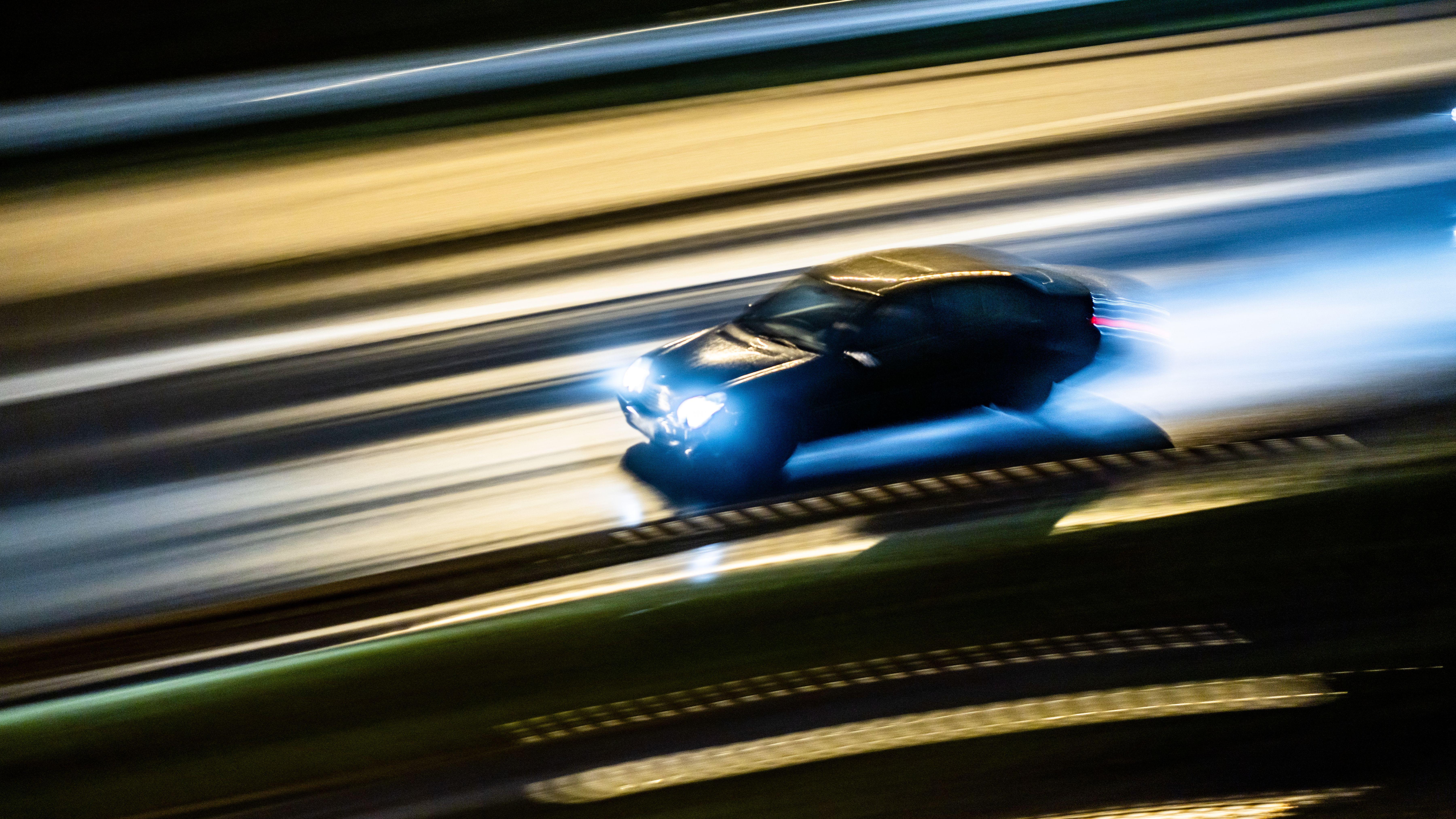 Schnell fahrendes Auto bei Nacht
