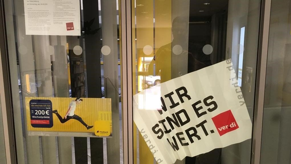 Ein Streikschild der Gewerkschaft Verdi vor dem Eingang einer Filiale der Postbank