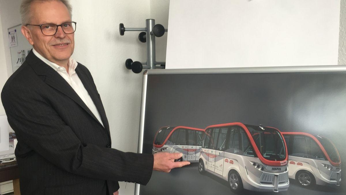 Projektleiter Ralf Borowsky deutet mit seinem Finger auf eine Abbildung, die drei autonom fahrende rot-silberne Busse zeigt.