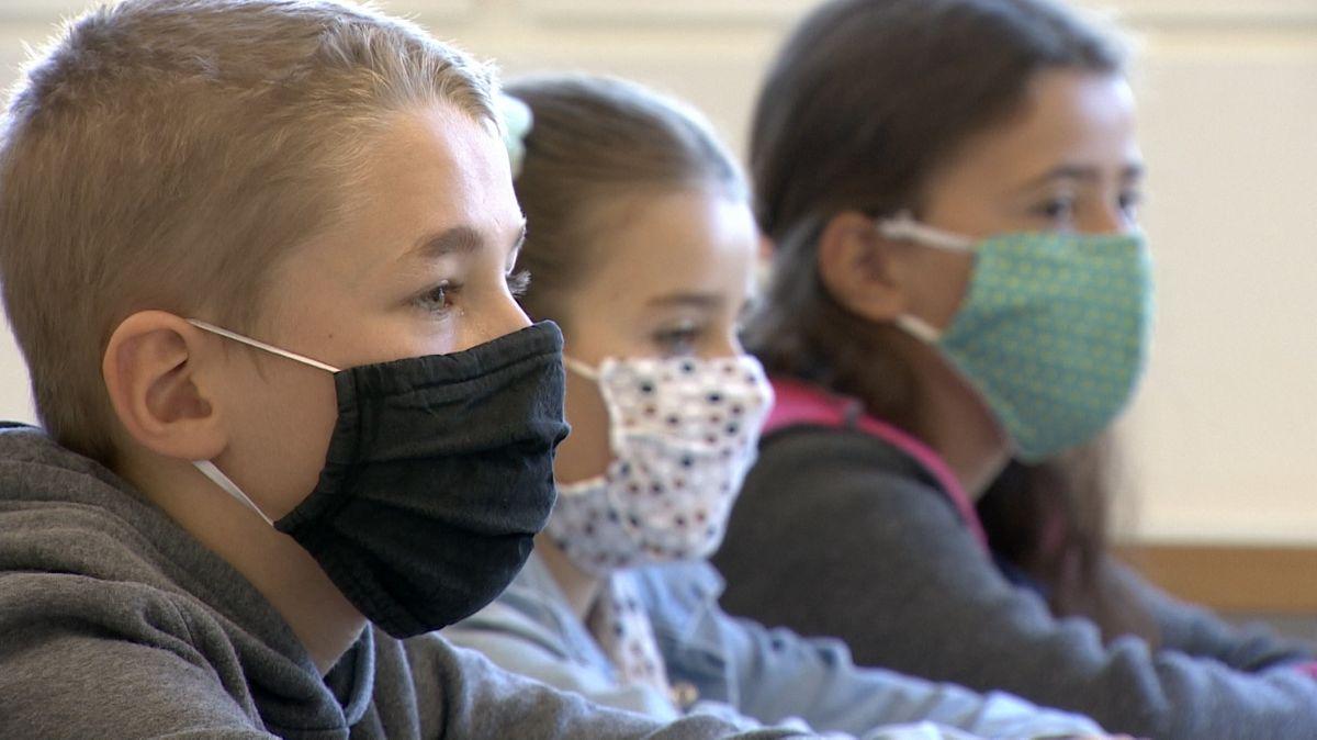 Drei Kinder tragen im Unterricht Schutzmasken