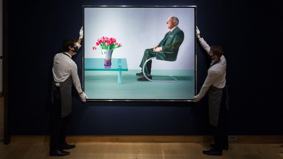 Zwei Mitarbeiter halten das Bild zur Präsentation in der Hand
