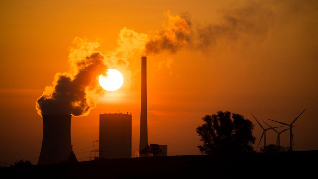 Die Sonne geht hinter einem Kohlekraftwerk auf.