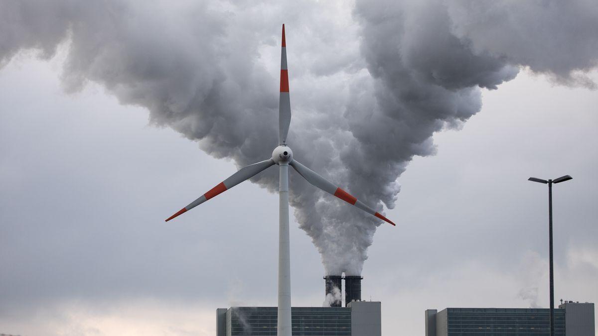Hamburg: Abluft steigt aus den Schornsteinen des Kohlekraftwerks Moorburg hinter einem Windrad in den Himmel.