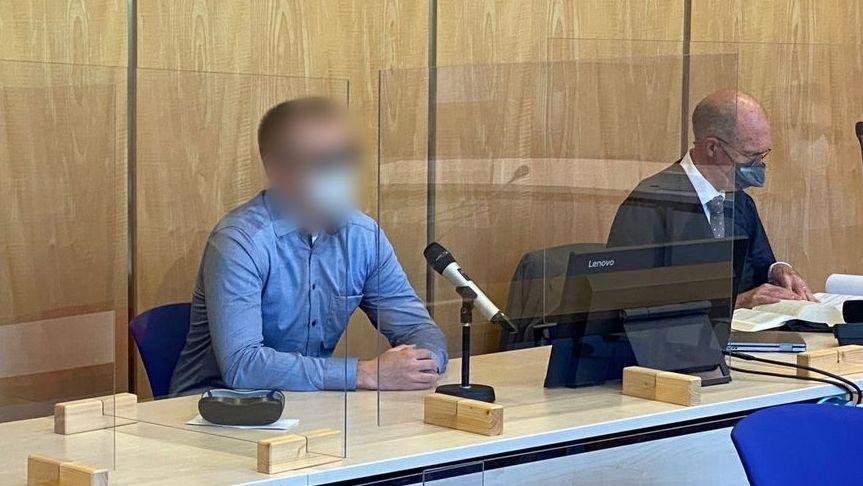 Der Angeklagte sitzt im Gerichtssaal hinter einer Fensterscheibe.