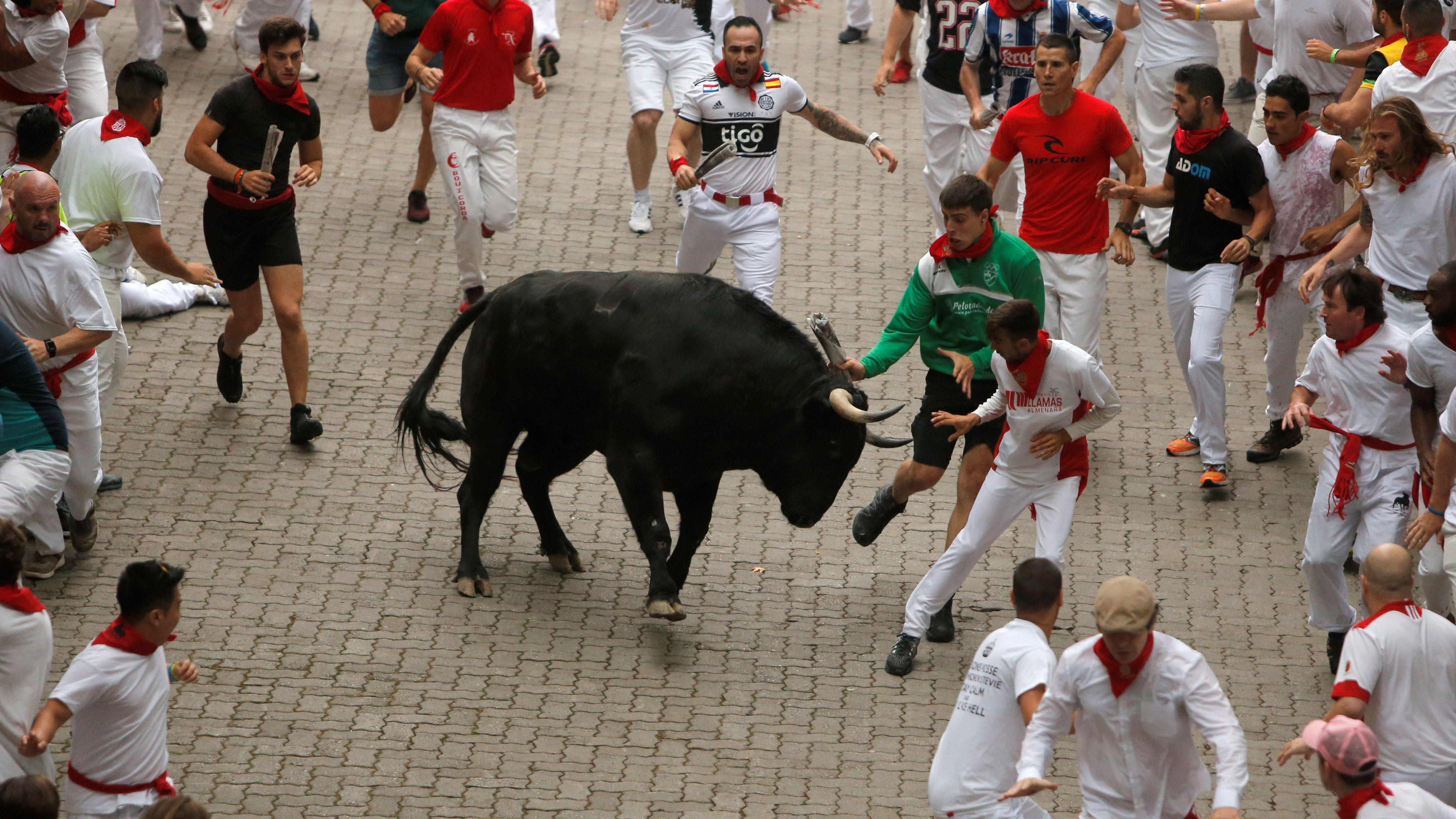 Läufer versuchen, einem Stier beim ersten Stierrennen auf dem Festival San Fermin in Pamplona auszuweichen.