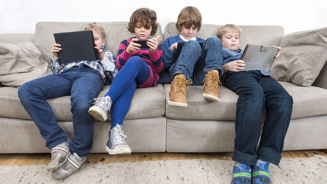 Vier Kinder mit Tablets und Smartphones sitzen auf einem Sofa