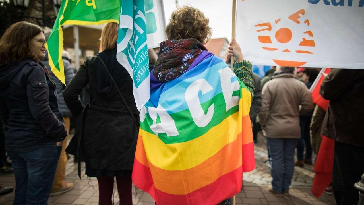 Mit einer umgehängten Friedensfahne steht eine Teilnehmerin des Ostermarsches bei einer Kundgebung