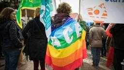 Mit einer umgehängten Friedensfahne steht eine Teilnehmerin des Ostermarsches bei einer Kundgebung | Bild:picture-alliance/dpa/Frank Rumpenhorst