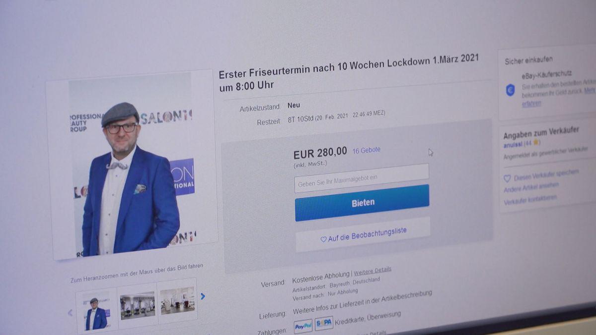 Auf der Internetseite ist Friseurmeister Andreas Nuissl im blauen Jacket und Fliege zu sehen, daneben ein Fenster, das die Versteigerung des ersten Friseurtermins nach dem Lockdown anzeigt.