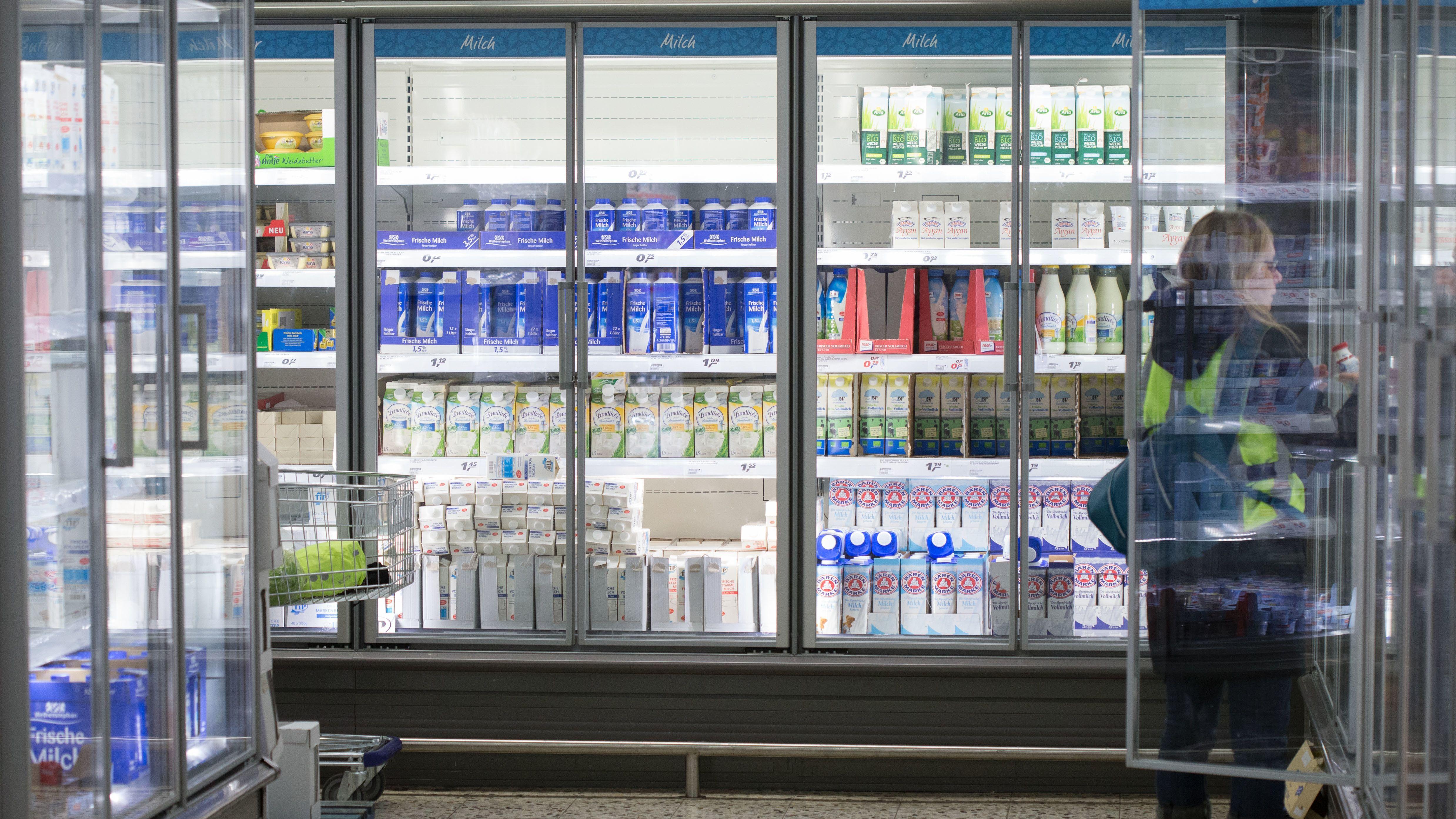 Eine Supermarkt-Kundin vor dem Milch-Regal