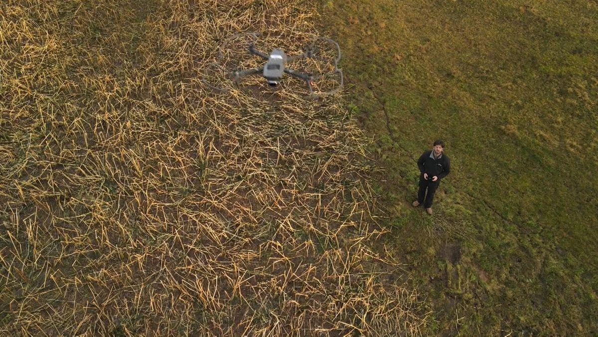 Eine Mann lässt eine Drohne steigen