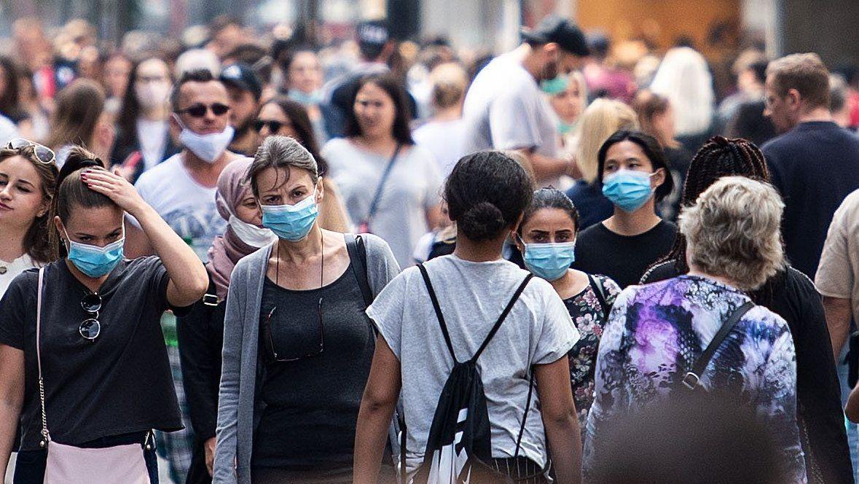 Menschen mit und ohne Maske laufen relativ dicht gedrängt auf einer Kölner Straße herum