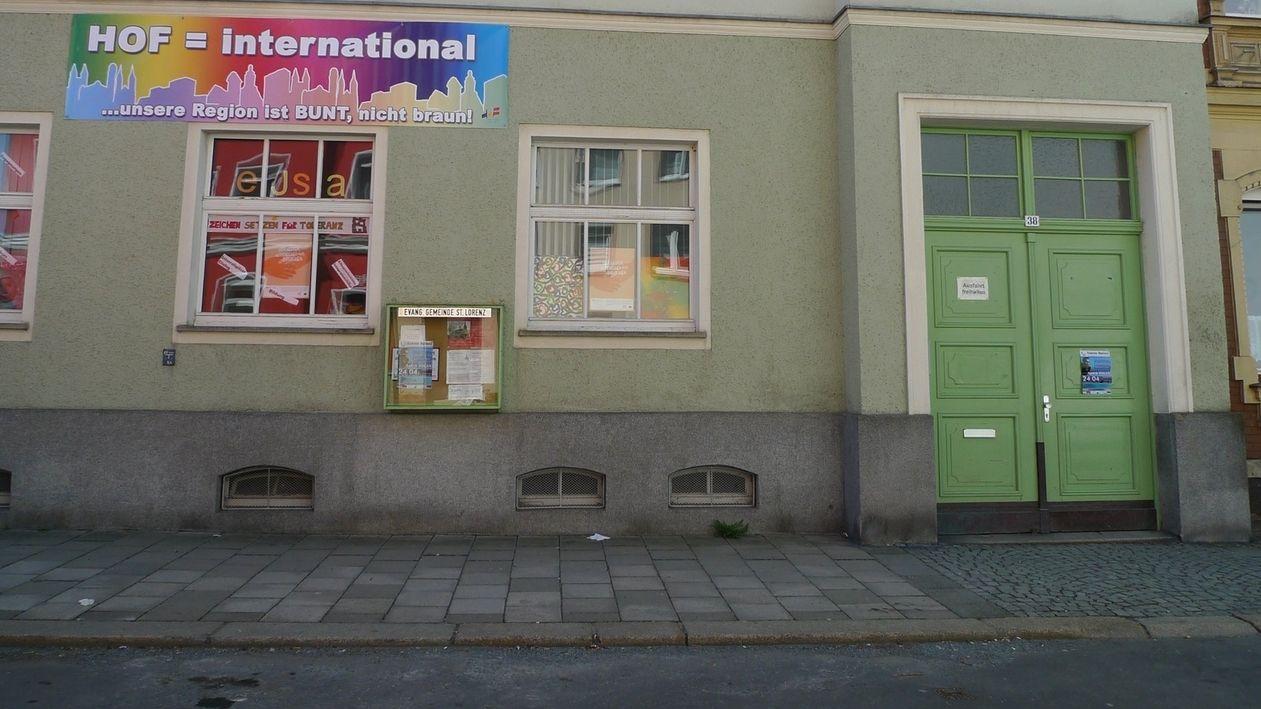 """Eine grüner Hausfront mit einem bunten Banner. Darauf steht: """"Hof = international""""."""