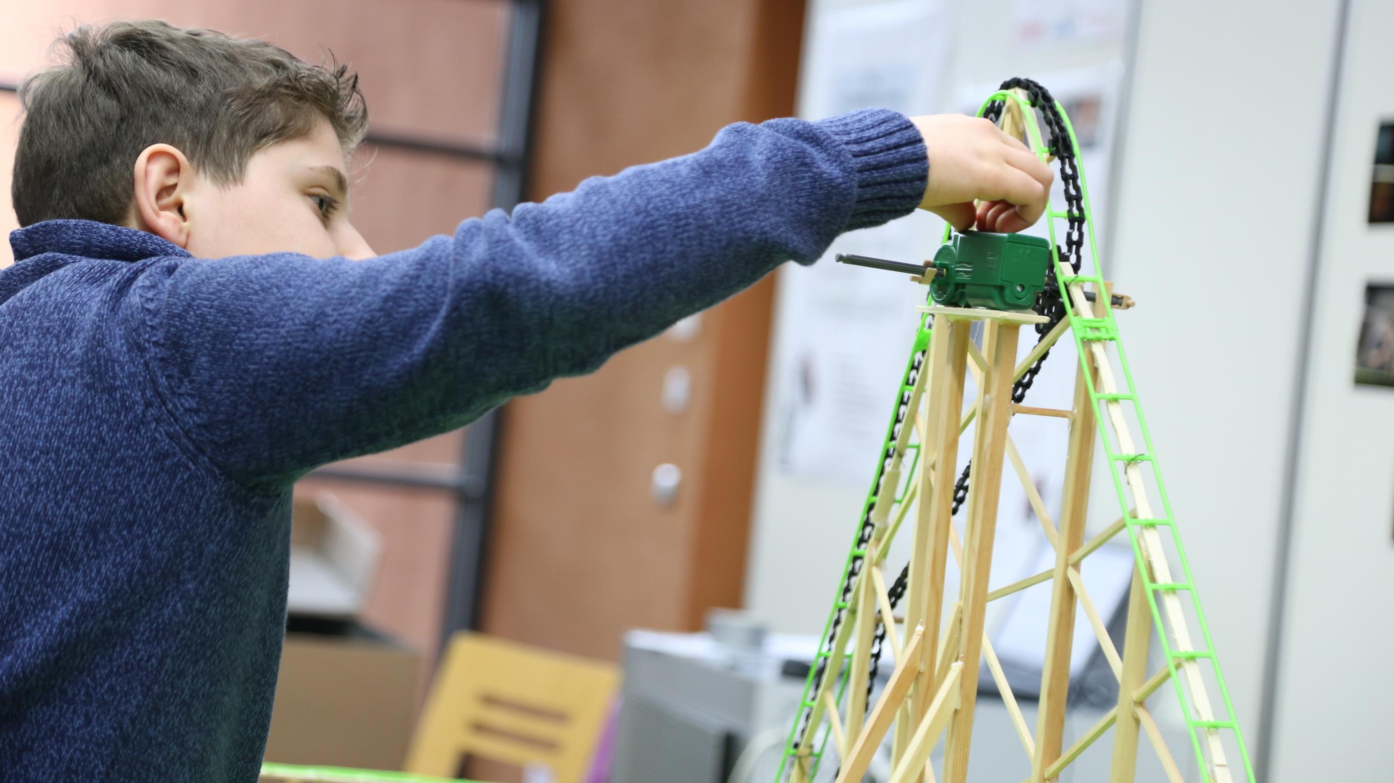 """Beim Wettbewerb """"Jugend forscht"""" in Hof experimentiert ein Junge an einer kleinen Achterbahn."""