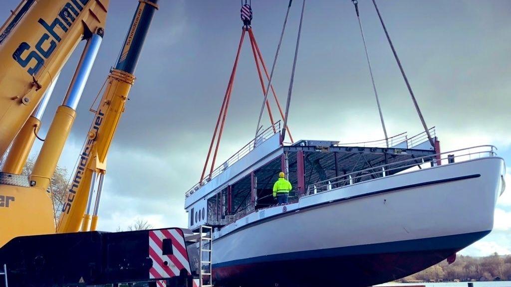 Neues Schiff am Starnberger See - Kran setzt an Tauen befestigtes Oberdeck auf den Schiffsrumpf