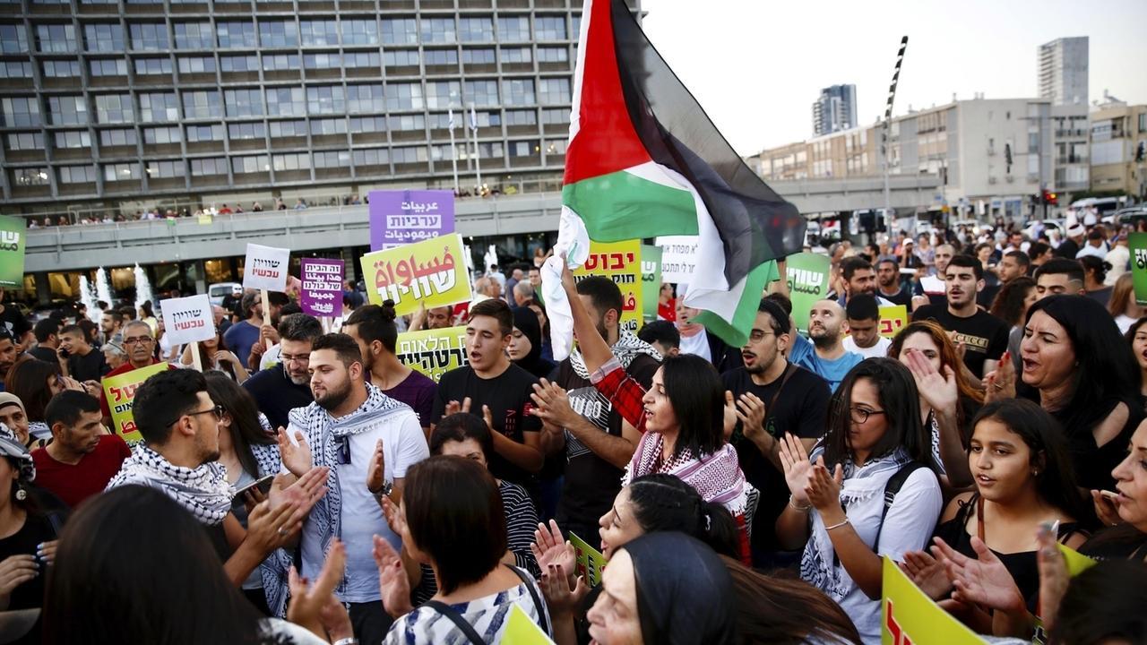 Eine große Zahl junger Leute protestiert mit der palästinensischen Fahne in Tel Aviv