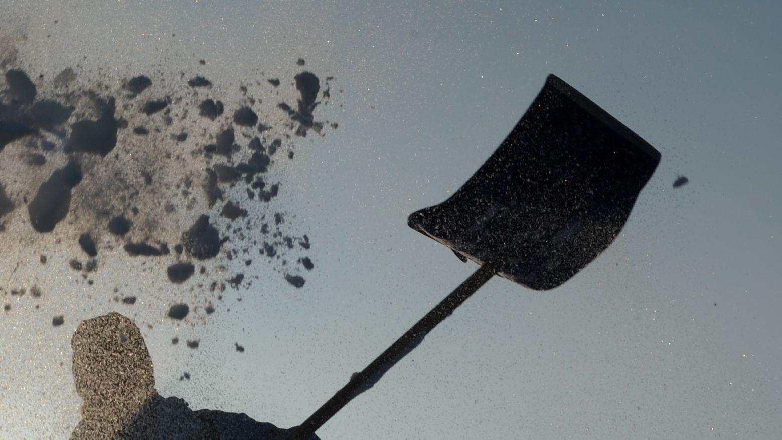 Ein Mann schwingt eine Schneeschaufel
