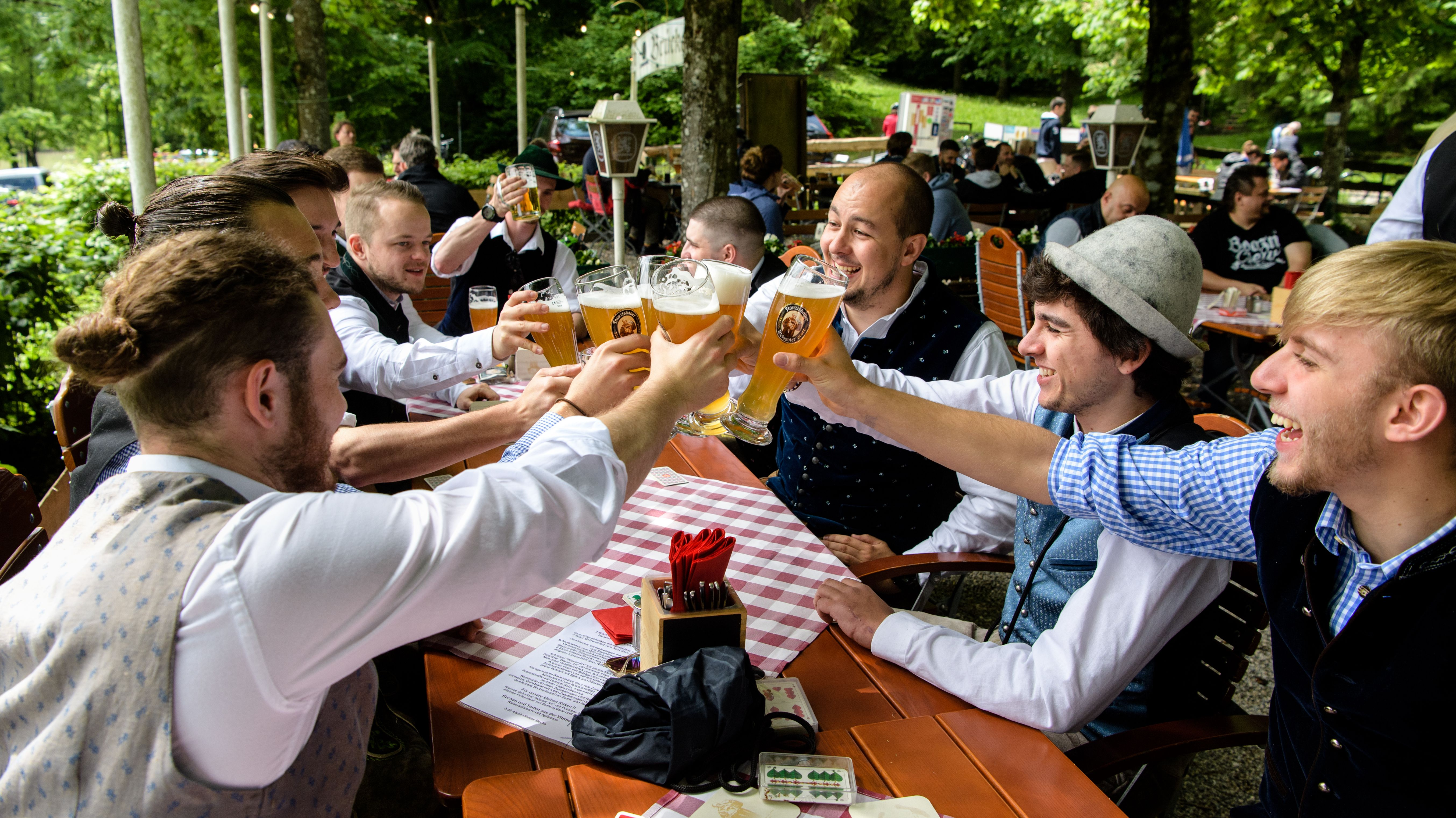 Männer stoßen in einem Biergarten an