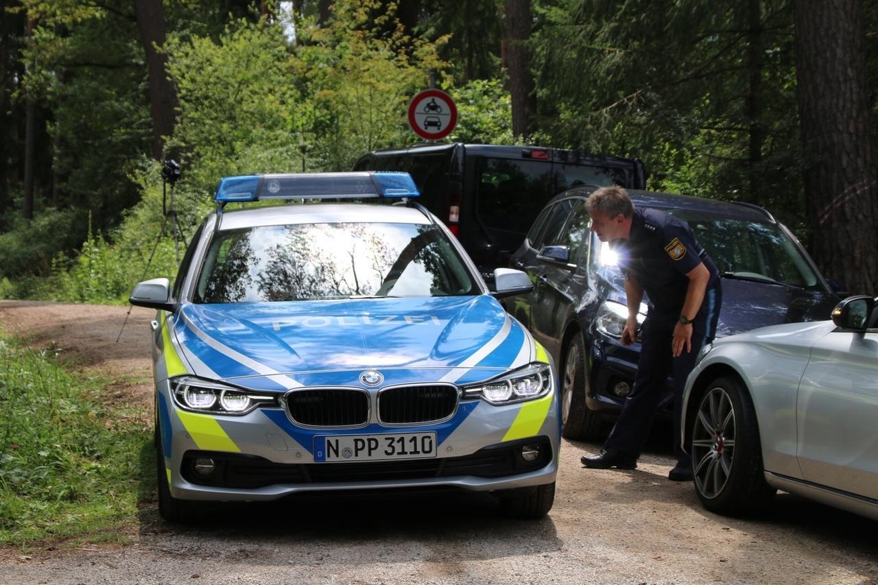 14.07.2019, Bayern, Lauf: Ein Polizist steht auf einem Waldweg an einem Einsatzfahrzeug der Polizei. In einem Wald im Landkreis Nürnberger Land ist ein toter Mann gefunden worden. Die Kriminalpolizei hat die Ermittlungen aufgenommen. Foto: Andreas Eberlein/dpa +++ dpa-Bildfunk +++