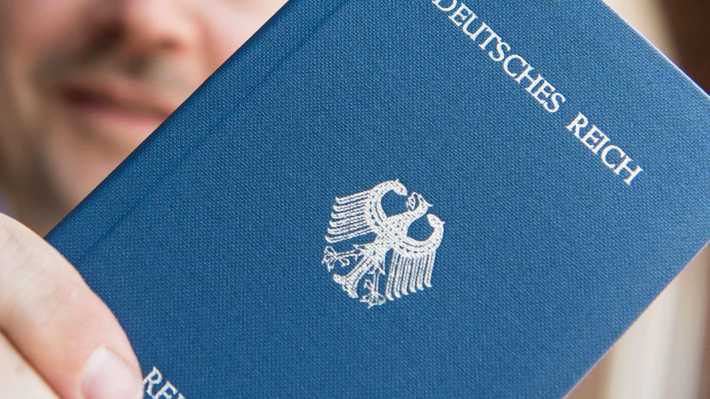 """""""Deutsches Reich Reisepass"""" ist auf dem Heft zu lesen, das ein """"Reichsbürger"""" zeigt."""